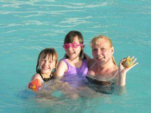 family enjoying solar heated pool